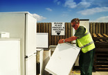 Recycling centre worker moving fridge at fridges and freezers recycling point