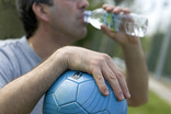 Football player drinking from plastic bottle