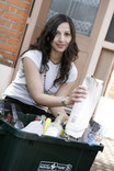 Woman recycling newspaper at kerbside recycling bin