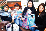 Family outside house with card, plastic bottles, shoes and aerosol cans for recycling