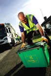 Crew member lifting green recycling bin on street with recycling lorry