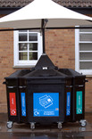 Communal recycling bins under cover outside building