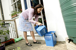 Woman emptying kitchen food waste caddy into outside caddy in garden