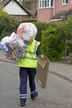 Man collecting clear recycling sacks and cardboard on street