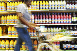 Woman pushing trolley past shelves of bottles of squash in supermarket