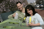 Man and woman recycling mixed plastic bottles at bring bank
