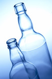 Two clear glass bottles on blue background