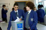 Two boys recycling paper in classroom recycling bin