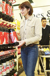 Woman choosing plastic bottle of Coca Cola in supermarket - man in background