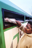 Woman putting newspapers in paper bring bank