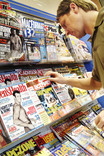 Man choosing computing magazine in supermarket