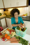 Woman in kitchen putting vegetable peelings into food waste caddy