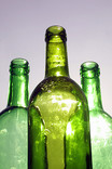 Line of three green glass bottles