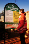 Woman reading recycling centre sign - Wandsworth