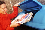 Woman recycling newspapers and magazines at a bring bank
