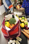 Loose fruit and vegetables and bottles packed in re-usable fabric bag on supermarket checkout