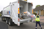 Throwing clear recycling sacks into recycling lorry