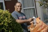 Man recycling plastic milk bottle outside house in orange recycling bag