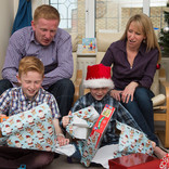 Family at Christmas - unwrapping presents