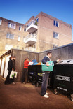 Group of people recycling at bring banks with flats in background