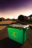 Green recycling bin on street with houses and sky