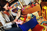 Woman with children's books, toys and games for re-use