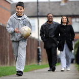 Parents and son walking with football