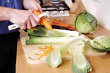 Peeling carrots and leeks in kitchen