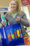 Woman packing shopping at checkout in re-usable shopping bag