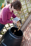 Woman emptying kitchen food waste caddy into compost bin