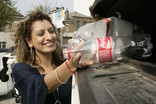 Woman recycling plastic bottles at bring bank