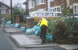 Man collecting green recycling bags on street