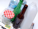 Assorted plastic bottles, green and brown glass bottles, clear glass jar, newspaper