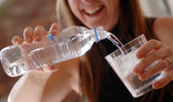 Woman pouring glass of water from plastic bottle