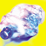 Crushed plastic water bottle on yellow background