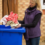 Woman putting Christmas wrapping paper into recycling wheelie bin