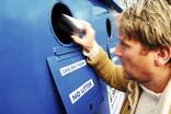 Man recycling can at bring bank