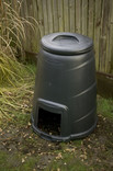 Black compost bin in garden