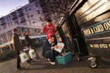 Group of people recycling at a row of bring banks with flats in the background - man sorting paper to recycle