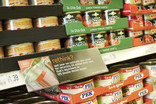 Shelves of tinned food in supermarket with recycling information on shelf label