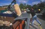 Man throwing cardboard into container at recycling centre