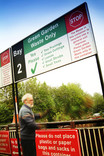 Man recycling garden waste at recycling centre, green garden waste sign
