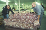 Two men lifting a second-hand sofa for re-use