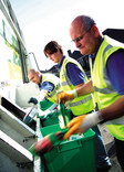 Crew emptying recycling bins into recycling lorry