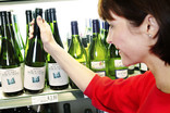 Woman choosing bottle of wine in supermarket - green bottle