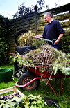 Man composting in garden with wheelbarrow