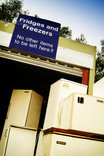 Stacked fridges and freezers and recycling centre with sign