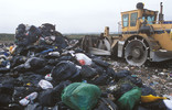 Landfill site with black bin bags and vehicle