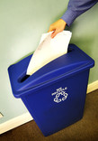 Putting paper into an office recycling bin