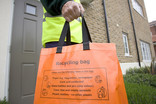 Man collecting orange recycling bag outside house